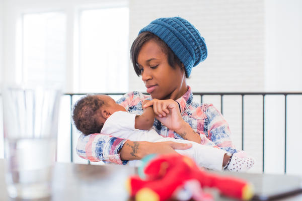 Mom Danielle cradles her baby Kori. Dr. Jim Greenbery says the way African-American women experience healthcare often leads to mistrust with the system and poor outcomes.