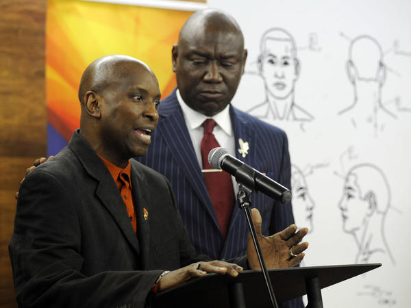 "Flanked by attorney Ben Crump, Emantic Bradford Sr. discusses the results of a forensic examination on his son Emantic ""EJ"" Bradford Jr., who was fatally shot by police after a shooting in a shopping mall on Thanksgiving Day, after being mistaken for a suspect."