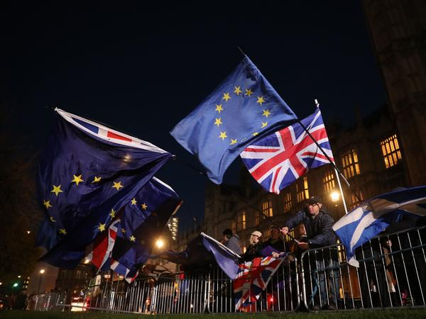 Anti-Brexit campaigners wave the Union Jack and European Union flags outside the Houses of Parliament on Wednesday.