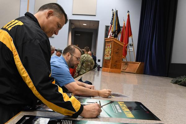 """Veterans sign the movie poster for """"Black Hawk Down: The Untold Story"""" at an October screening at Fort Drum, N.Y."""