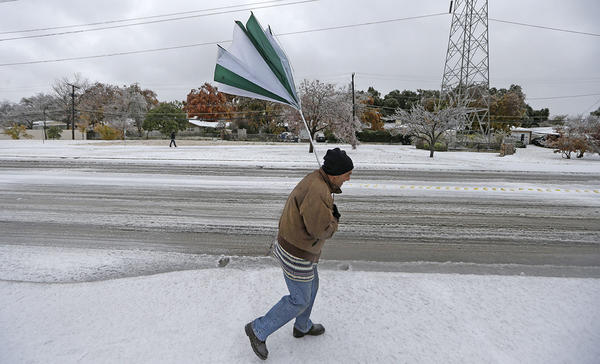A gust of wind collapses a pedestrian's umbrella in Dallas, Dec. 6, 2013.