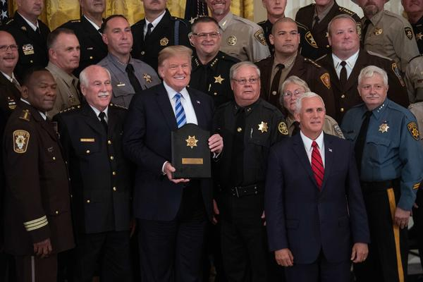 President Trump, with Vice President Pence, poses with a plaque given to him by sheriffs from across the country during a meeting in September. Trump has campaigned as a strong advocate for law enforcement.