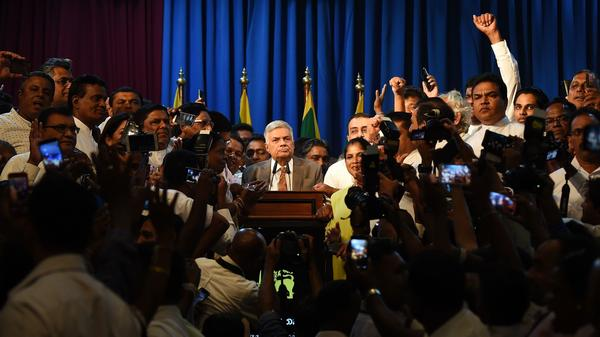 Ranil Wickremesinghe, seen behind the lectern, speaks to his supporters at the prime minister's official residence Sunday in Colombo. His reinstatement as prime minister concludes weeks of political chaos prompted by his firing.