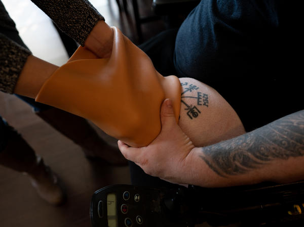 Caretaker Ashlee Williams helps her husband, Former Staff Sgt. J.D. Williams, begin the process of putting on a prosthetic leg.