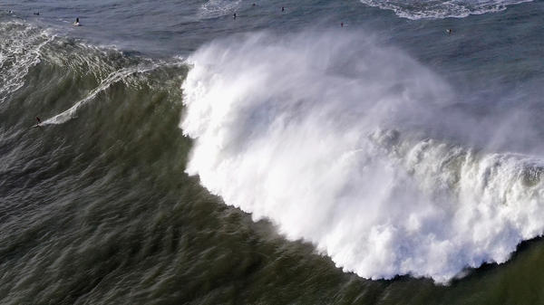 """A surfer rides a wave at Mavericks off Half Moon Bay, Calif., on Monday. The NWS warned of waves that could reach """"50+ feet at favored breaks"""" in Northern California."""