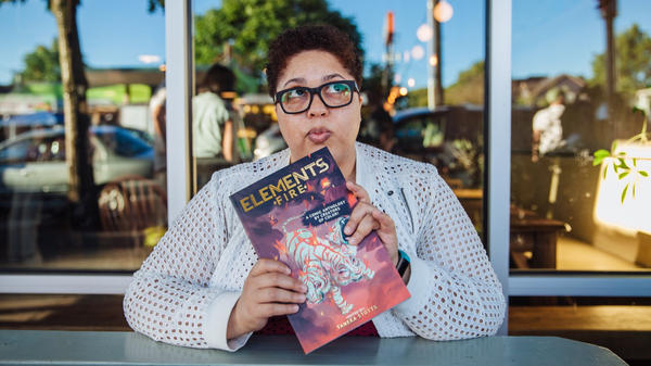 Creator Taneka Stotts holds a copy of her Eisner Award-winning anthology <em>Elements: Fire</em>.
