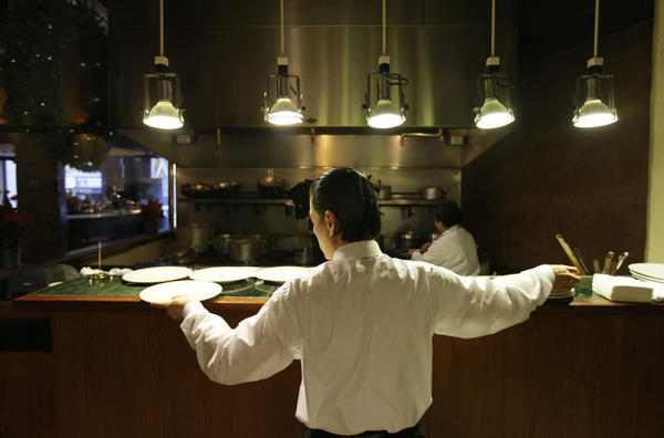 A waiter reaches for plates at a restaurant in San Francisco. Nearly all restaurants in the U.S. operate under the tip system: Servers and those in the back of the house — chefs, line cooks, dishwashers, etc. — are paid a lower-than-average standard minimum wage, and then they earn tips to make up for the pay disparity. (Eric Risberg/AP)