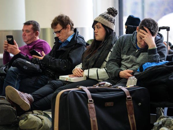 Passengers wait Friday at London's Gatwick Airport, where drone sightings repeatedly caused flights to be delayed and suspended at the height of holiday travel season.