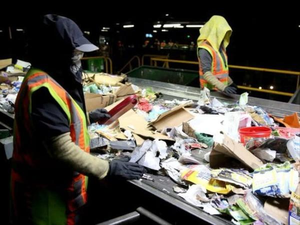 <p>Recycling sorters pull non-recyclables off a conveyer belt at Garten Services in Salem on Thursday, Jan. 11, 2018.</p>
