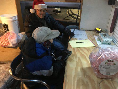 Rob Kinucan helps Marcus Ramirez, 10, talk with Santa Claus over a ham radio.