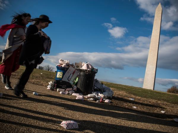 Tourists walk past a public dustbin, spilling with litter, next to the Washington Monument on the National Mall in Washington, D.C. on Dec. 24, 2018.
