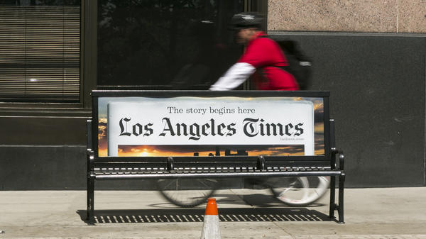 A cyclist rides on the sidewalk past the Los Angeles Times building in downtown Los Angeles. The paper's Saturday deliveries were affected by an interference with Tribune Publishing's print production systems.