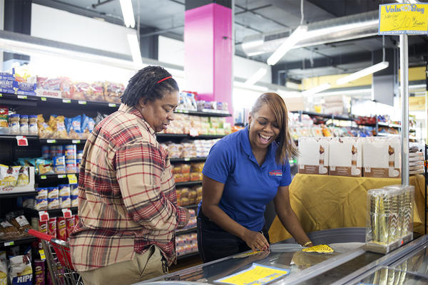 Evelyn Fluellen, manager of Neighbors' Market, helps Chestina Taylor, left, pick out meat at the East St. Louis grocery store on Tuesday morning.