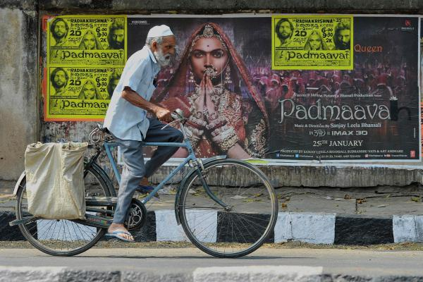 A cyclist rides past a poster of the controversial film <em>Padmaavat</em> in Bangalore on Thursday.
