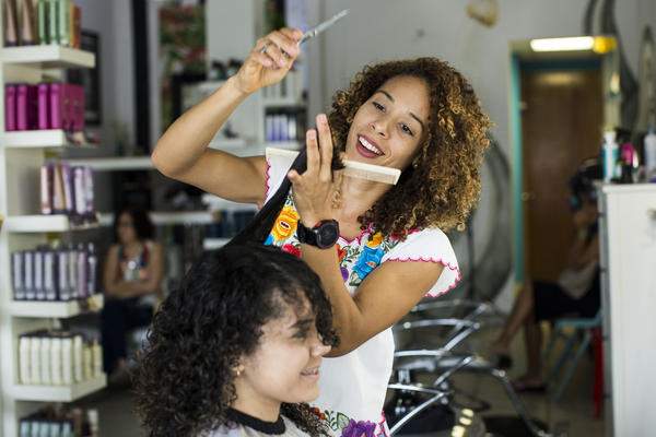 "Gerlin Santos cuts Lisney Santiago's hair at Laura Om Studio in San Juan, Puerto Rico, on Saturday. Santos left her curls natural four years ago and is the only one in her family who quit straightening her hair. For Santiago, 21, leaving her curls has given confidence. ""It even gives me more security in myself; it makes me unique. I like it,"" Santiago says."
