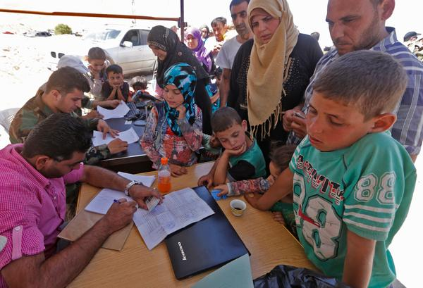 Syrian refugees get an identity check on the Lebanese side of the al-Zamrani crossing between Lebanon and Syria on Thursday.