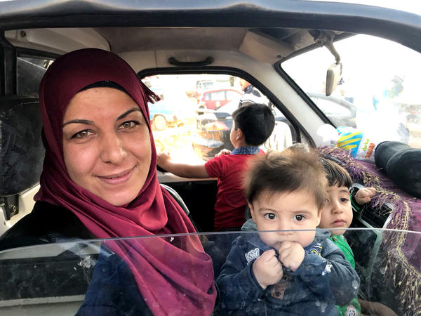 Hala, a Syrian refugee, cradles her children in the car ahead of her journey back to Syria.