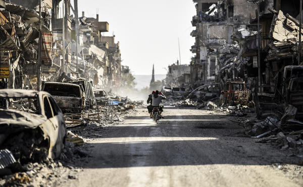 """A Syrian youth uses his cellphone to film the destroyed vehicles and heavily damaged buildings down a street in Raqqa on Oct. 20, 2017, after a Kurdish-led force expelled ISIS fighters from the northern Syrian city, formerly the group's """"capital."""""""
