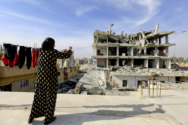 """A Syrian woman hangs laundry in Raqqa, the former """"capital"""" of the Islamic State group in Syria, on Jan. 11."""