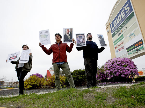 Protestors holding pictures of people who died from use of paint removers, including Drew Wynne, protest outside a Portland, Maine, Lowe's store on May 10, 2018. They were trying to persuade the retailer to stop selling paint strippers containing methylene chloride.