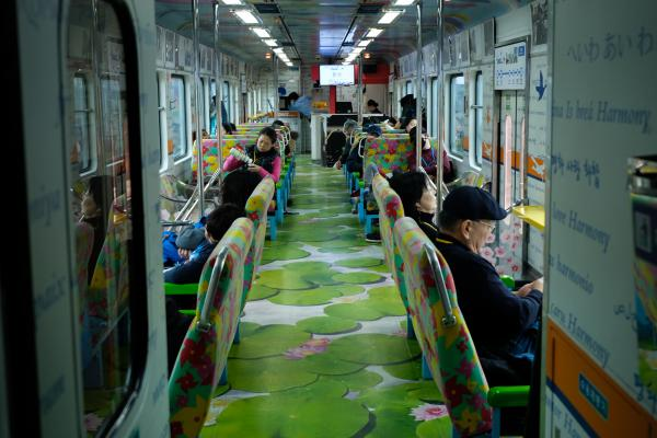"The interior of the DMZ train, a three-car tourist train. It is decorated with words such as ""love,"" ""peace"" and ""harmony,"" in several languages."