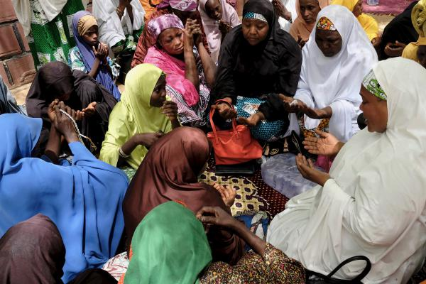 Women gather to pray outside the Dapchi emir's palace, a few miles from the girls' school where 110 students were kidnapped on the night of Feb. 19. Wearing a pink shawl and a troubled gaze, Rebecca Sharibu is among the distraught parents.