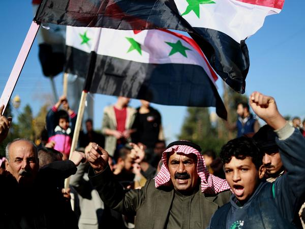Syrian demonstrators wave the national flag during a demonstration in the Kurdish-majority city of Qamishli in northeastern Syria on Sunday, asking for the Syrian army's protection as Turkey threatens to carry out a fresh offensive following the U.S. decision to withdraw troops.