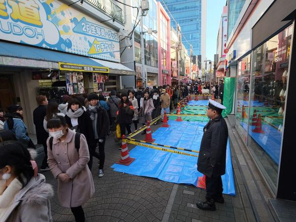 A policeman stands next to a roped-off crime scene the morning after a man drove into the crowd on New Year's Eve on Takeshita Street in Tokyo's fashion district of Harajuku on Tuesday.