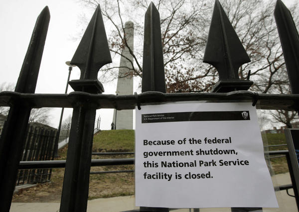 A sign is posted on a fence near an entrance to the Bunker Hill Monument, Monday, Dec. 24, 2018, in Boston. The historic site, erected to commemorate the Revolutionary War Battle of Bunker Hill, and run by the National Park Service, was closed due to a partial federal government shutdown. (Steven Senne/AP)