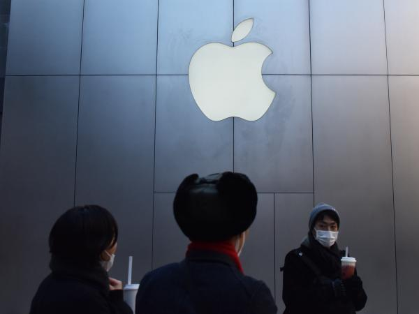 People walk past an Apple store in Beijing in December 2018. Apple CEO cited weaker-than-expected iPhone sales in China as the company lowered its quarterly revenue estimates Wednesday.
