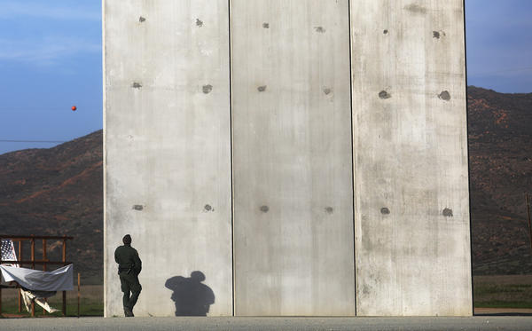 A U.S. Border Patrol agent walks toward one of President Trump's border wall prototypes on the U.S. side of the U.S.-Mexico border on Jan. 9, 2019, as seen from Tijuana, Mexico. (Mario Tama/Getty Images)