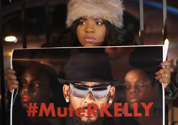 """A demonstrator holds up a sign reading """"#MuteRKelly"""" at a protest outside the singer's Chicago studio in January 2019, just days after the release of the Lifetime mini-series <em>Surviving R. Kelly.</em>"""