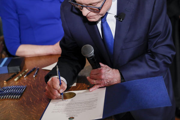 Gov. Mike DeWine signs oath of office document along with several executive orders.