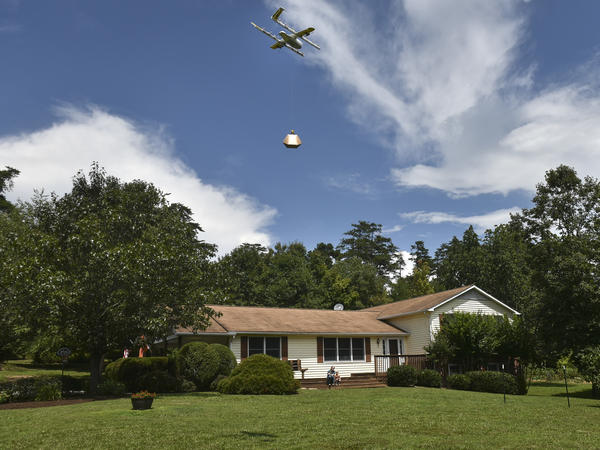Federal regulators have announced plans to allow drone operators to fly their unmanned aerial vehicles over populated areas and at night. A Wing Hummingbird drone from Project Wing arrives and sets down its package at a delivery location in Blacksburg, Va., last year.