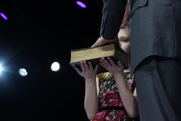 State Treasurer Michael Frerichs' daughter holds a bible while her father takes the oath of office.