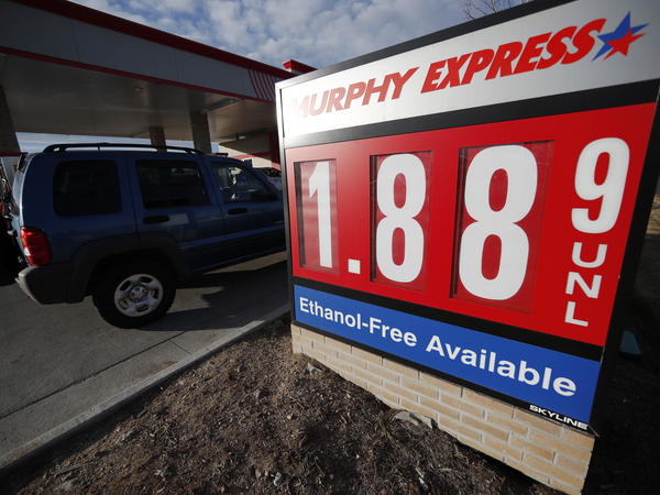 Motorists drive past a sign advertising regular gasoline at $1.88 per gallon at a station in Longmont, Colo., on Dec. 22, 2018. Falling gasoline prices have given drivers a little extra cheer this winter.