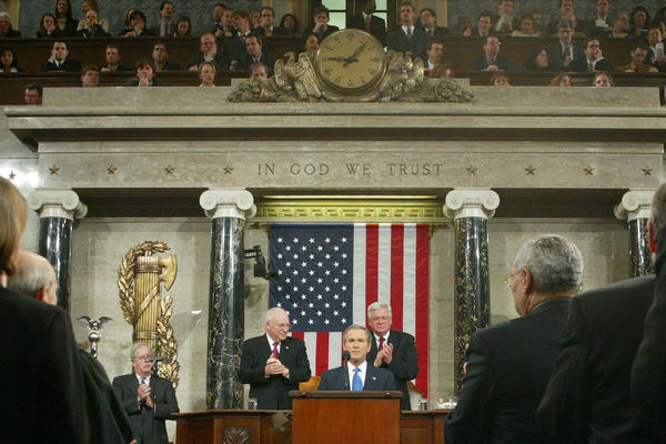 "President George W. Bush flanked by Vice President Dick Cheney (left) and Speaker of the House Dennis Hastert, delivers his second State of the Union address in 2003 at the Capitol building in Washington D.C. President Bush emphasized the importance of disarming Saddam Hussein, one year after he declared Iraq to be part of an ""axis of evil."""