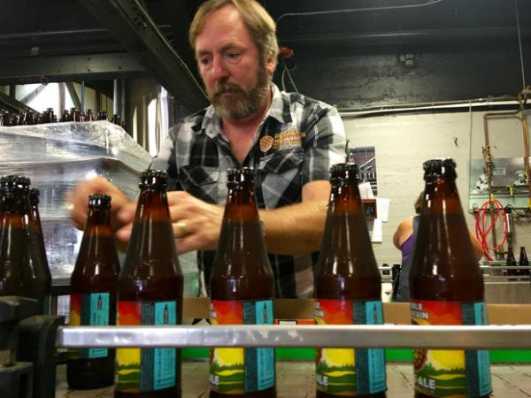 <p>Double Mountain Brewery founder Matt Swihart grabs freshly bottled pale ale from the bottling line in Hood River. The brewery's new beer is among the first to be sold in Oregon's new refillable beer bottles.</p>