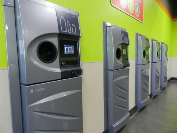 A row of sparkling clean reverse vending machines greet customers at the grand opening of the Medford BottleDrop center.