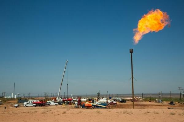 A flare burns on May 24, 2018, atop a drill pad on land near Carlsbad. The oil-rich Permian Basin straddles West Texas and southeastern New Mexico.  Robin Zielinski for the Center for Public Integrity/Via The Texas Tribune