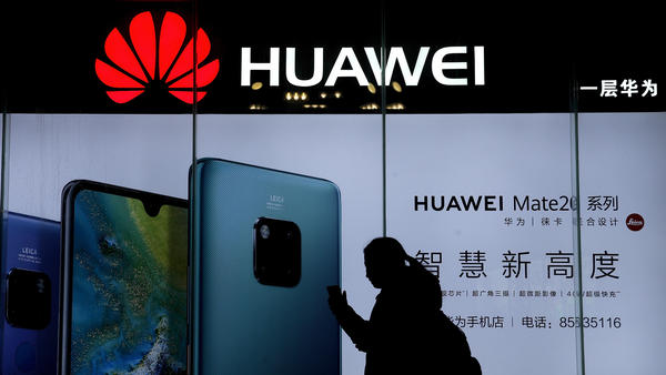 A woman browses her smartphone as she walks by a Huawei store at a shopping mall in Beijing. The telecom giant is at the center of a geopolitical feud between China and the United States.