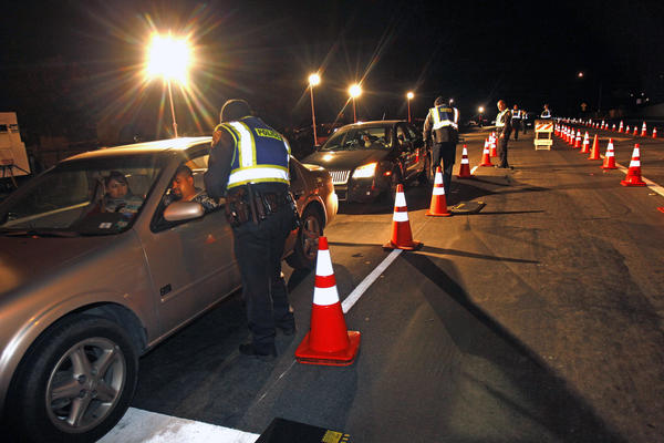 Police officers check drivers at a sobriety checkpoint in Escondido, Calif.