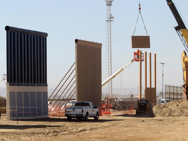 Crews work at the construction site of prototypes for President Trump's border wall in San Diego County.