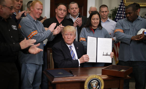 Surrounded by steel and aluminum workers, President Trump holds up the order on steel imports that he signed in Roosevelt Room at the White House on Thursday.