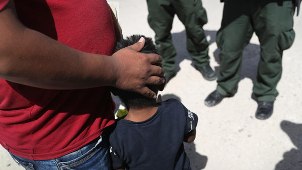 U.S. Border Patrol agents take a father and son from Honduras into custody at the U.S.-Mexico border near Mission, Texas, on Tuesday.