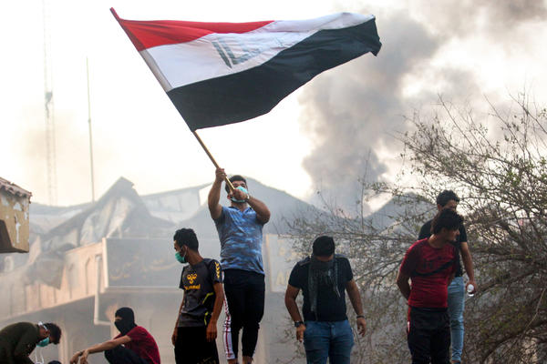 An Iraqi protester waves a national flag while demonstrating outside the burnt-down local government headquarters in the southern city of Basra on Sept. 7, during demonstrations over problems including poor public services.