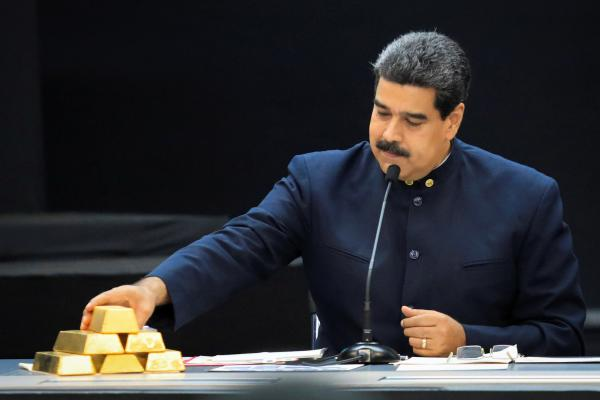 Venezuelan President Nicolás Maduro touches a gold bar as he speaks with economic officials at Miraflores Palace in Caracas in March.