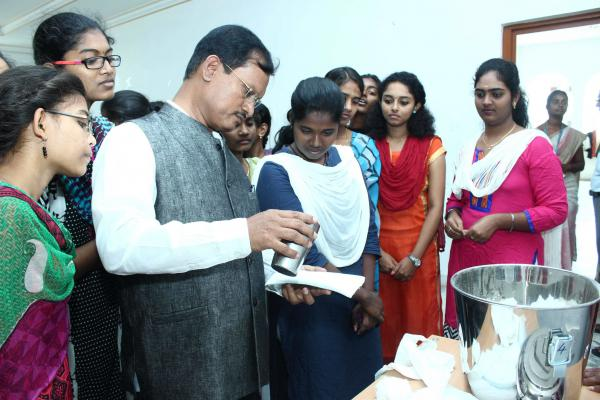 Arunachalam Muruganantham, inventor of a menstruation pad machine, tests the quality of the pads as local women, who are eager to learn how the machine works, look on.