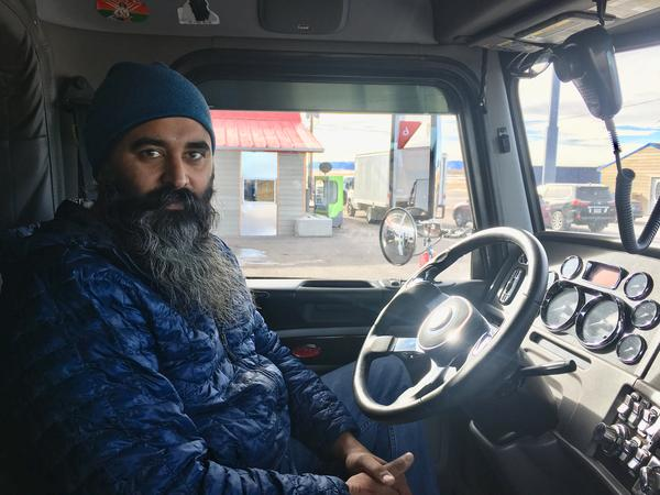 Driver Mintu Pandher sits in his truck at A&C Truck Stop outside Laramie, Wyoming.