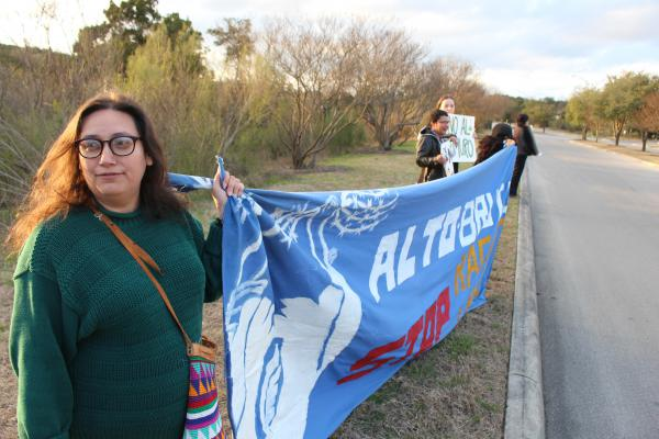 """Diana Lopez of the Southwest Workers Union leads a chant near the entrance to the JW Marriott Hill Country Resort, where Fox News' """"Battle at the Border"""" event was held"""
